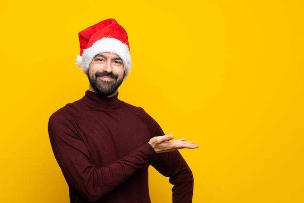 Man with christmas hat over isolated yellow background presenting an idea while looking smiling towards