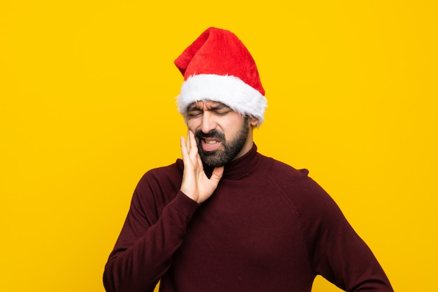 Man with christmas hat over isolated yellow background with toothache
