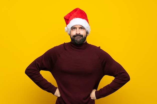 Man with christmas hat over isolated yellow wall angry
