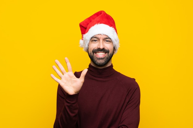 Man with christmas hat over isolated yellow wall counting five with fingers