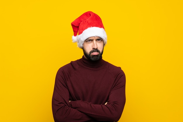 Man with christmas hat over isolated yellow wall feeling upset