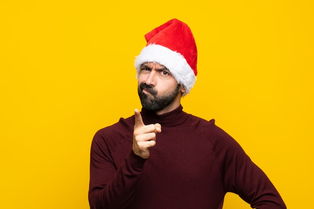 Man with christmas hat over isolated yellow wall frustrated and pointing to the front