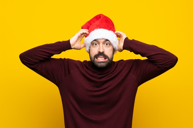 Man with christmas hat over isolated yellow wall frustrated and takes hands on head