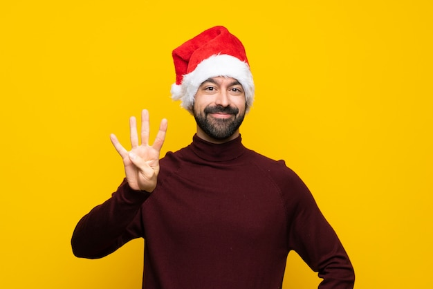 Man with christmas hat over isolated yellow wall happy and counting four with fingers