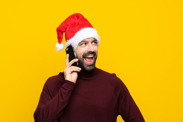 Man with christmas hat over isolated yellow wall keeping a conversation with the mobile phone
