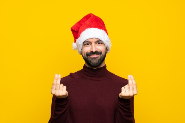 Man with christmas hat over isolated yellow wall making money gesture