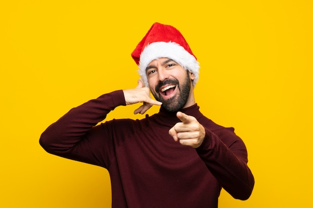 Man with christmas hat over isolated yellow wall making phone gesture and pointing front