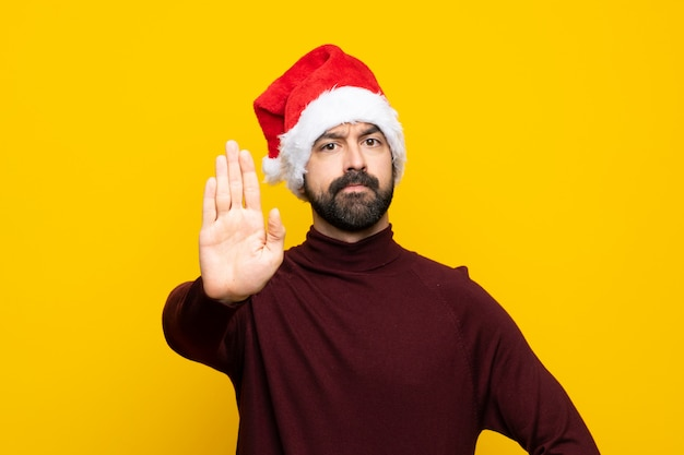 Man with christmas hat over isolated yellow wall making stop gesture