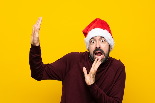 Man with christmas hat over isolated yellow wall nervous and scared