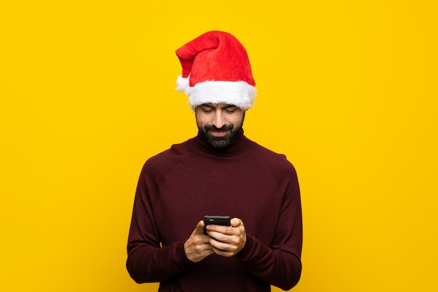 Man with christmas hat over isolated yellow wall sending a message with the mobile