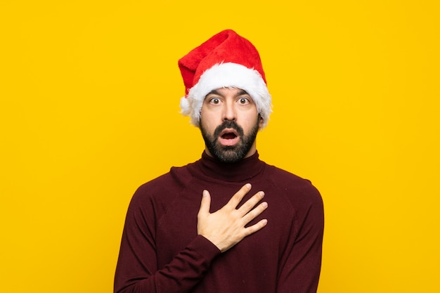 Man with christmas hat over isolated yellow wall surprised and shocked while looking right