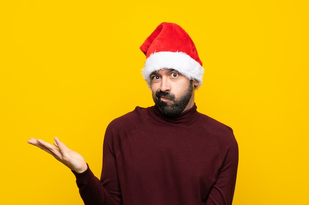 Man with christmas hat over isolated yellow wall unhappy for not understand something