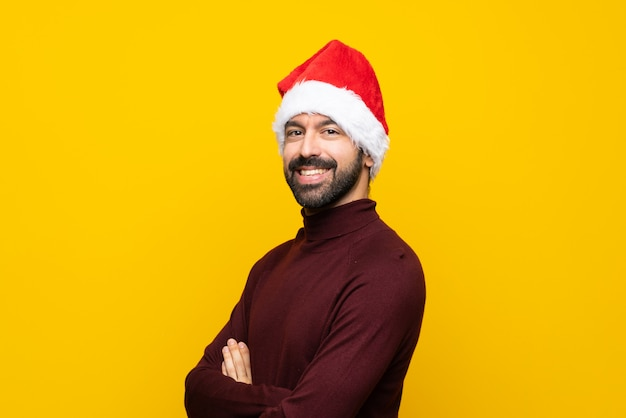 Man with christmas hat over isolated yellow wall with arms crossed and looking forward