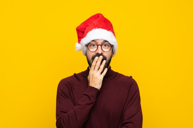Man with christmas hat over isolated yellow wall with glasses and surprised