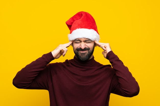 Man with christmas hat over isolated yellow wall with headache