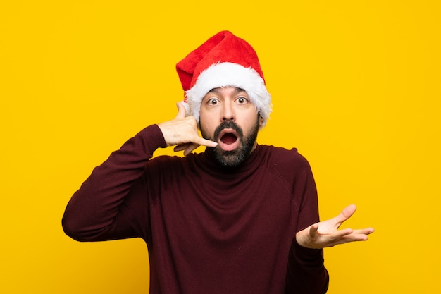 Man with christmas hat making phone gesture and doubting