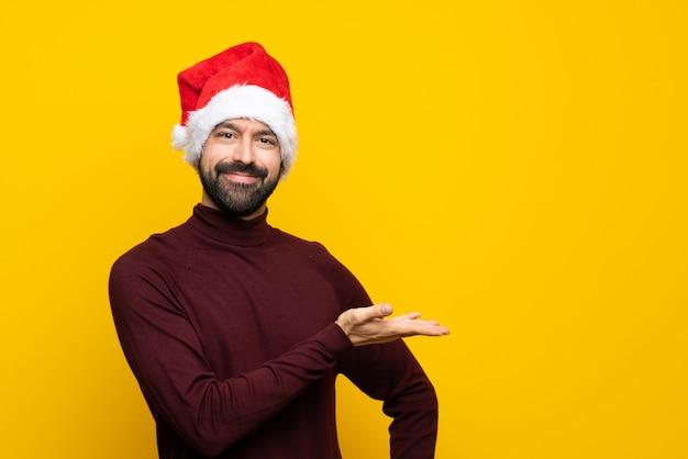 に向かって笑顔を見ながらアイデアを提示する分離の黄色の背景の上のクリスマス帽子の男