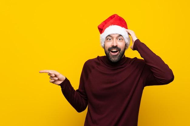 驚きと側に指を指している孤立した黄色の壁の上のクリスマス帽子の男