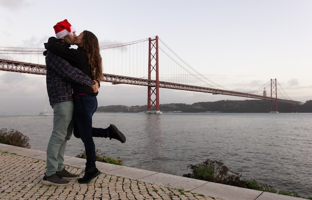 Man with christmas hat and woman kissing by 25 de abril bridge in lisbon portugal tourism concept