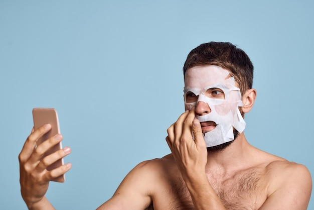 A man with a cleansing mask on his face examines himself in a mirror on a blue background