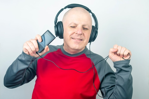Man with closed eyes listens to music with headphones on a light background