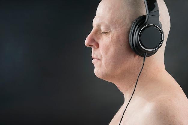닫힌 눈을 가진 남자는 어두운 배경에서 헤드폰으로 음악을 듣는