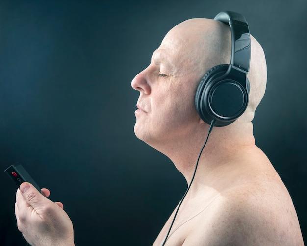 닫힌 눈을 가진 남자는 어둠 속에서 헤드폰으로 음악을 듣는