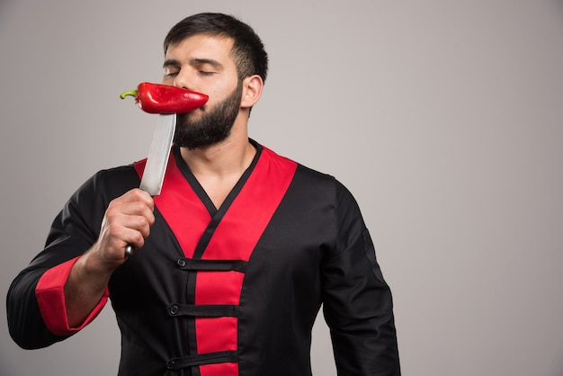 Man with closed eyes sniffs a red pepper on knife.