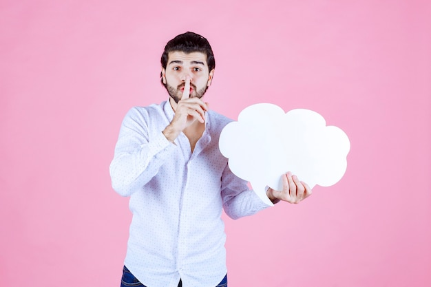 Man with a cloud shape board asking for silence.