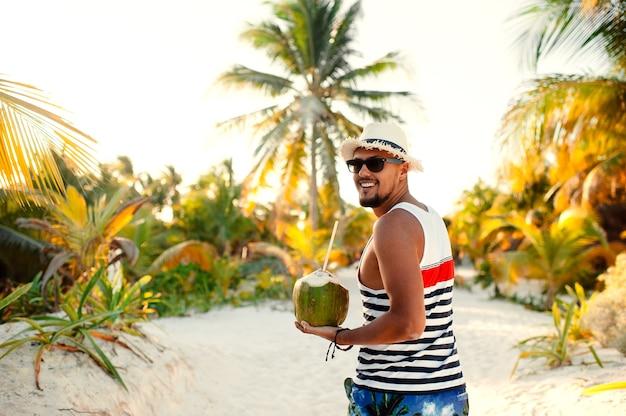 Человек с кокосом на тропическом пляже в солнечный летний день во время отпуска