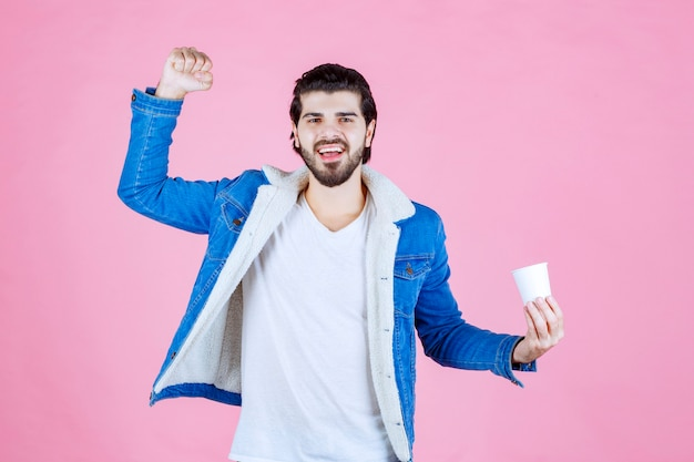 Man with a coffee cup demonstrating his fist