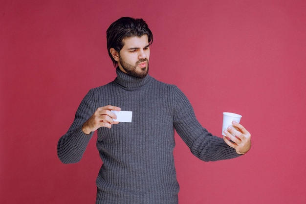 Man with a coffee cup showing his bill or business card.