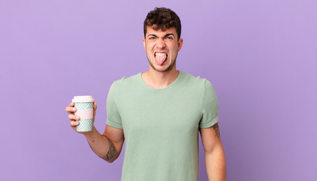 Man with coffee feeling disgusted and irritated, sticking tongue out, disliking something nasty and yucky