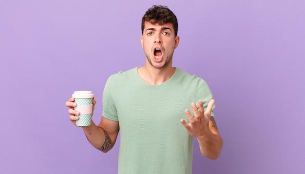 Мужчина с кофе чувствует себя чрезвычайно шокированным и удивленным, встревоженным и паническим, с напряженным и испуганным взглядом