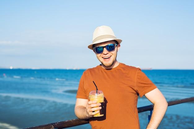 自由時間の休暇を楽しんで自由に海の近くでコーヒーフラッペを持つ男