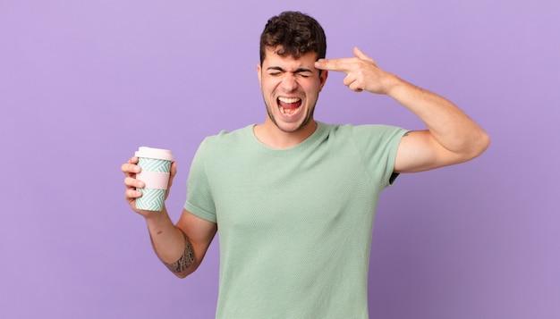 커피를 들고 불행하고 스트레스를 받는 남자, 손으로 총기 표시를 하고 머리를 가리키는 자살 제스처