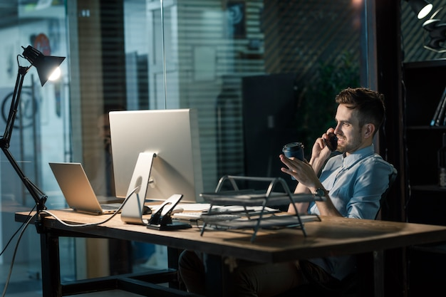 Man with coffee speaking phone late in office