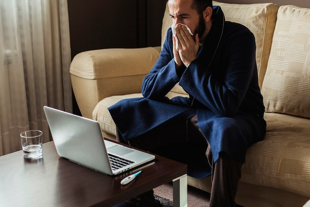 Man with a cold making an online medical consultation with his doctor from home