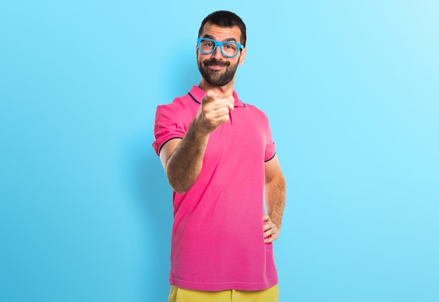 Man with colorful clothes pointing to the front on colorful background