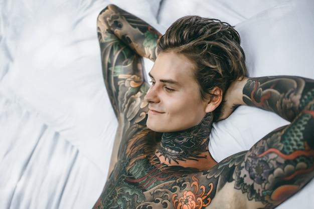 Человек с красочными татуировками, опираясь на белый лист