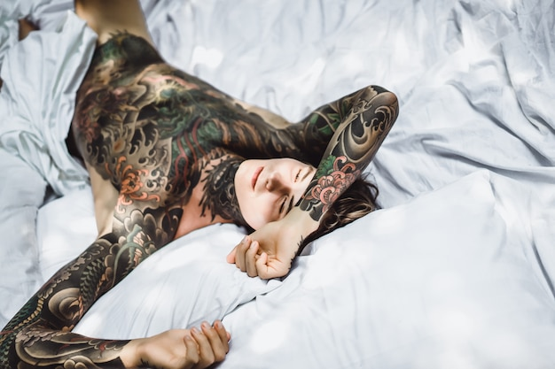 Man with colorful tattoos resting on a white sheet