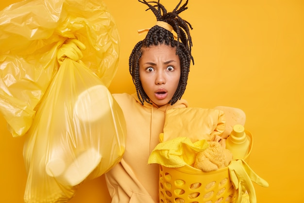 Man with combed dreadlocks carries bag full of litter laundry basket wears sweatshirt does domestic duties poses on yellow