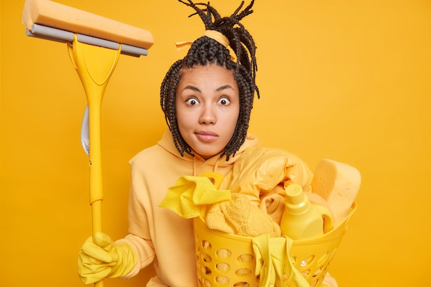 Man with combed dreadlocks stares impressed holds mop and full laundry basket isolated on yelloe