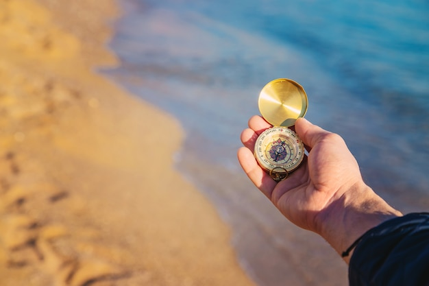 A man with a compass in his hands near the sea. selective focus.