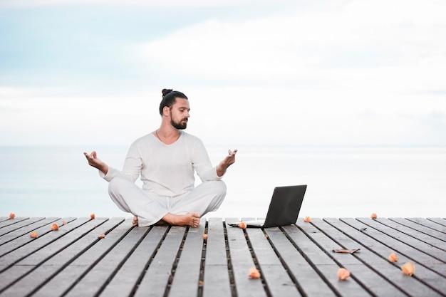 海の近くの木造の桟橋でヨガを瞑想するコンピューターを持つ男