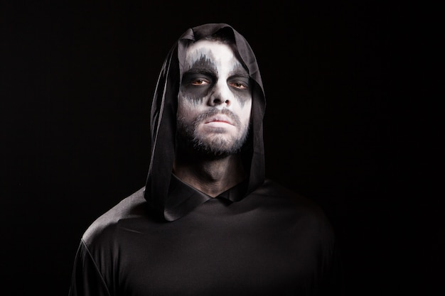 Man with creepy face dressed up like grim reaper over black background.