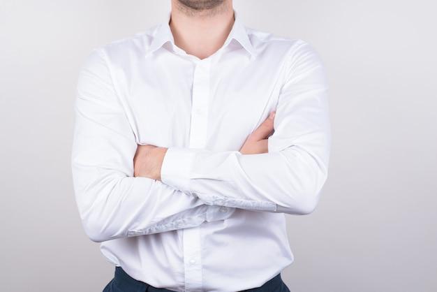 Человек со скрещенными руками в белой рубашке изолировал серый фон