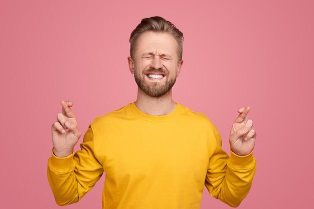 ピンクの背景に交差した指を持つ男