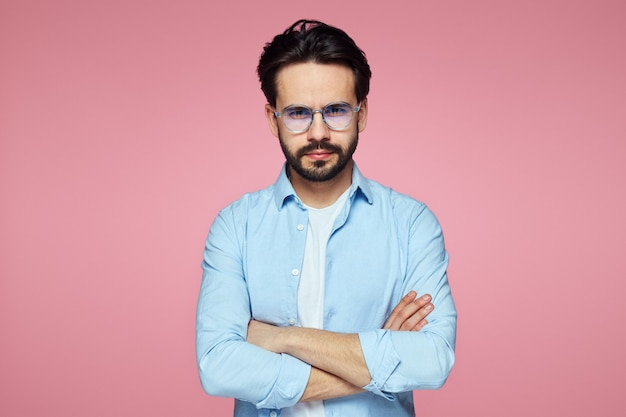 교차 손으로 남자는 분홍색 벽에 캐주얼 블루 셔츠를 착용