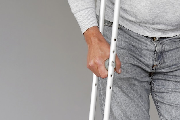 Man with crutch. close-up. front view